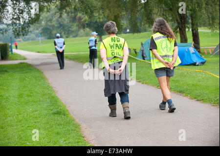 Newport, UK. 5th September 2014. Two PLO's (Police Liason Officers) walk past the Peace Camp at Tredegar Park followed - Stock Photo