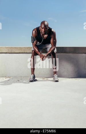 Portrait of a exhausted runner sitting outdoors. Muscular and fit young athlete relaxing after his fitness training. - Stock Photo