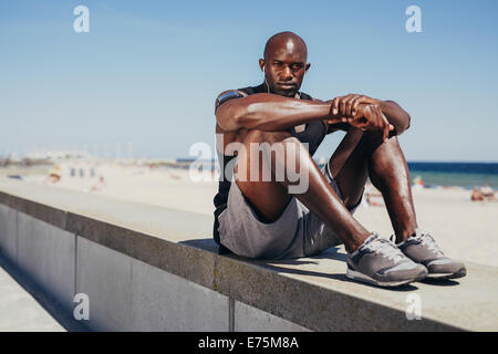Portrait of fit young athlete relaxing on sea wall looking at camera. Muscular African man resting after his workout. - Stock Photo