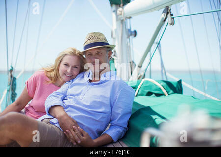 Couple sitting on deck of sailboat - Stock Photo
