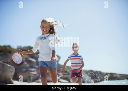 Young girl and boy running along beach - Stock Photo