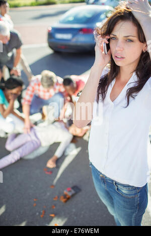 Woman calling emergency services at car accident - Stock Photo