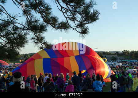 A crowd watches as a rainbow colored hot air balloon is inflated in Colorado Springs, CO - Stock Photo