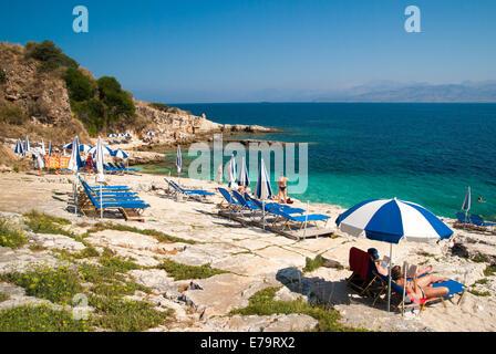 Sunbeds and umbrellas (parasols) on a rocky beach in Corfu Island, Ionian Sea, Greece - Stock Photo