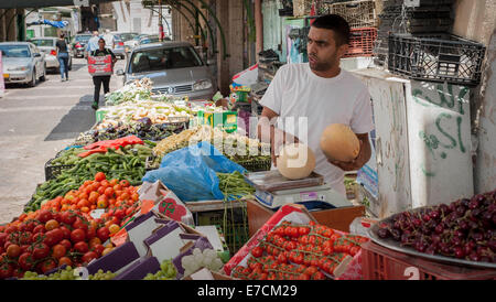 A vegetables vendor at his stand, old market in the old city of Nazareth, Israel - Stock Photo