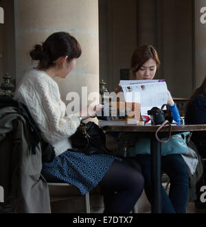 2 asian girls in the Louvre cafe - Stock Photo