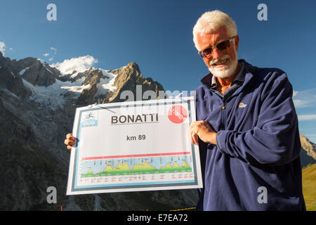 Walkers doing the Tour Du Mont Blanc outside the Bonatti Hut opposite the Grande Jorasses in the Italian Alps, holds - Stock Photo