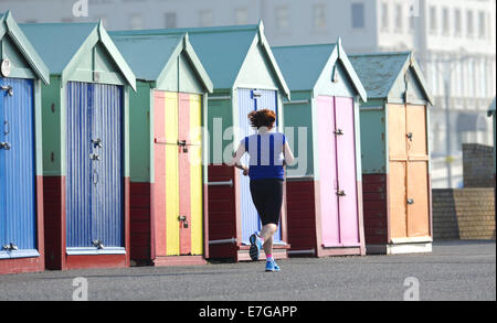 Hove Brighton Sussex UK 17 September 2014 - A runner passes Hove beach huts early this morning as temperatures were - Stock Photo