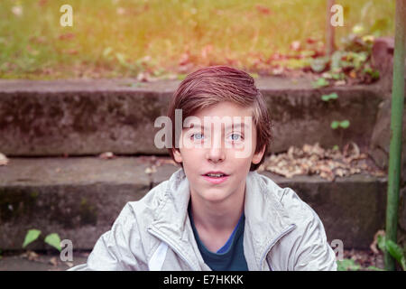 smiling teenager boy sitting on stairs in a park - Stock Photo