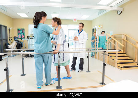 Physical Therapist Assisting Patient In Walking - Stock Photo
