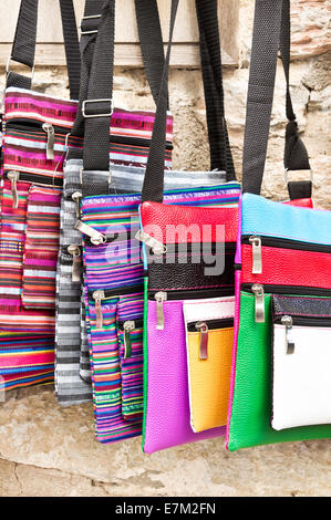 Colorful hand made bags on sale at a market - Stock Photo