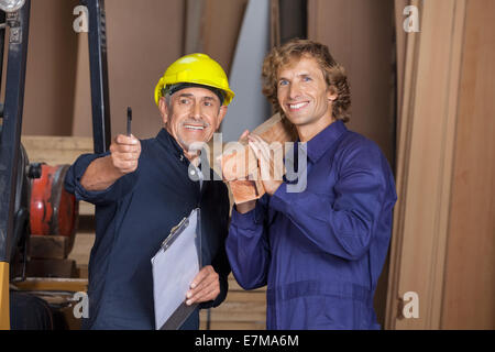 Carpenter Showing Something To Coworker Carrying Planks - Stock Photo
