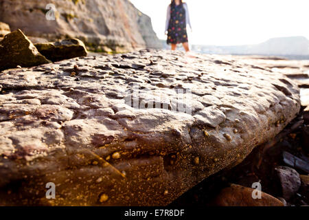 A close up of a rock with an out of focus woman standing in the background - Stock Photo