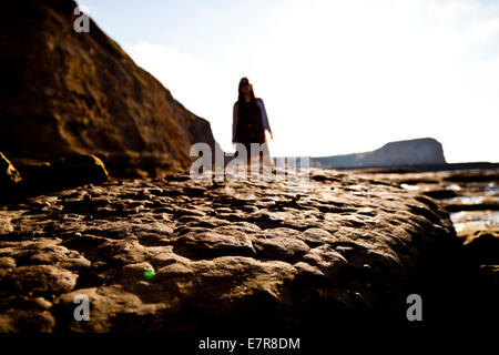 A close up of a rock with an out of focus, unidentifiable woman standing in the background - Stock Photo