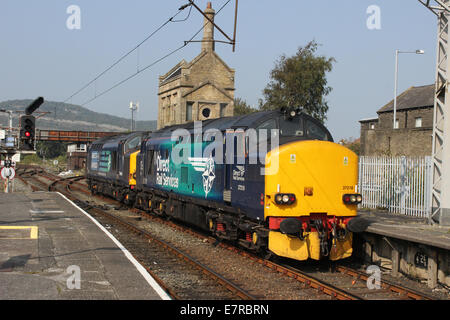 Two class 37 diesel locomotives in Direct Rail Services livery entering Carnforth station en route to Heysham Power - Stock Photo
