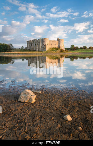 Carew Castle in Pembrokeshire, Wales. Mirror like reflections in the waters of the tidal mill that surround it - Stock Photo