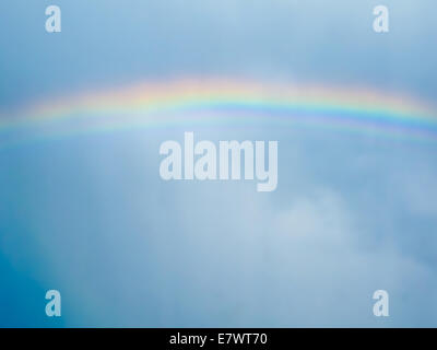 Rainbow across cloudy sky after rain. Stockholm, Sweden. - Stock Photo