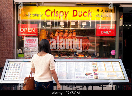 Young woman looking at the menu outside a Chinese restaurant, Gerrard Street, Chinatown Soho, London UK - Stock Photo