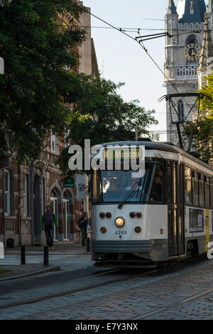 Tram is passing cobble street in Ghent on a sunny morning - Stock Photo