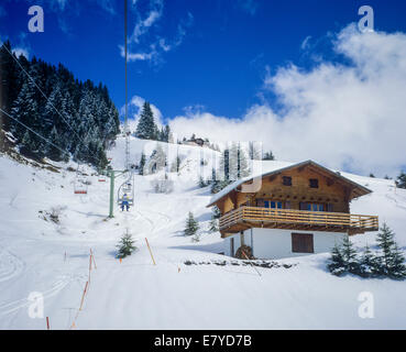 Chairlift and snowy chalet Morgins ski resort Les Portes du Soleil Swiss Alps Canton Valais Switzerland Europe - Stock Photo