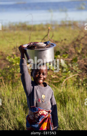 A young child carries a bucket of fish in a fishing village in Bangweulu Wetlands, Zambia - Stock Photo