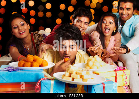 indian friends diwali Eating Sweets - Stock Photo