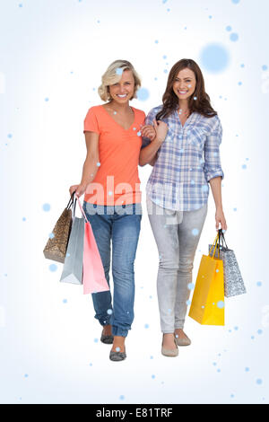 Composite image of two cheerful friends with shopping bags - Stock Photo