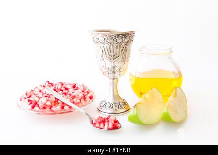 Rosh Hashanah Kiddush cup honey pomegranate and sliced apple - Stock Photo
