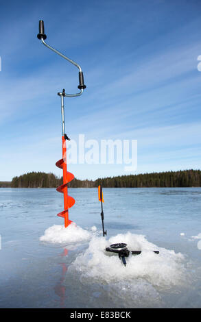 Hand ice auger and tip-up ice fishing rod , Finland - Stock Photo