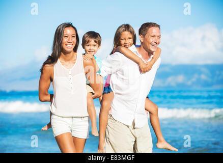 Happy Portrait of Mixed Race Family on the Beach - Stock Photo