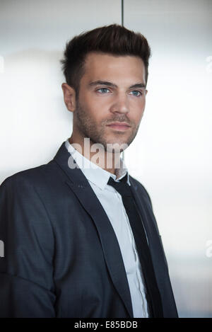 Young businessman waiting for elevator - Stock Photo