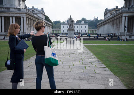 October 2014: Two women looking over the Statue of George II in the grounds of the University of Greenwich - Stock Photo