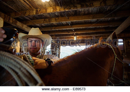 Rancher adjusting saddle on horse in barn - Stock Photo