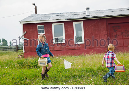 Brother and sister with butterfly net outside house - Stock Photo