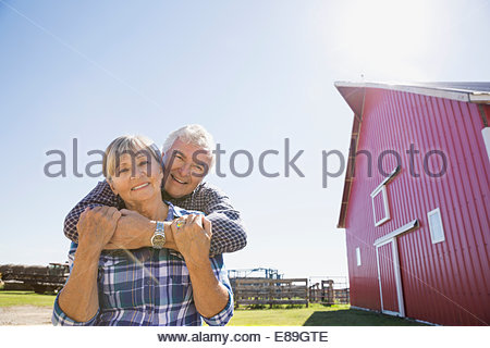 Portrait of couple hugging outside barn on farm - Stock Photo