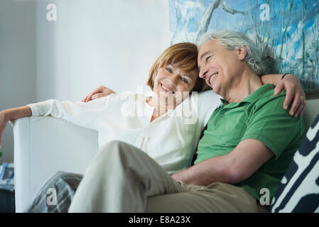 Couple relaxing on couch, smiling - Stock Photo