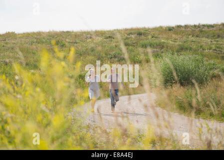 Mature couple running on field in summer - Stock Photo