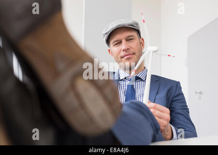 Portrait of businessman with wind power model - Stock Photo