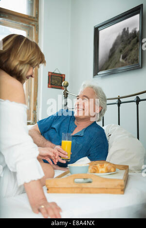 Couple having breakfast in bed, smiling - Stock Photo