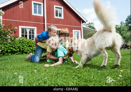 Father and sons pet dog playing on grass - Stock Photo