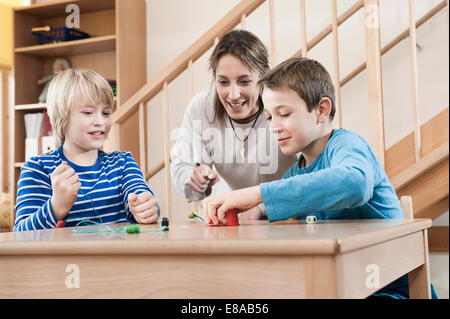 Portrait of two playing boys and female childcare assistant - Stock Photo