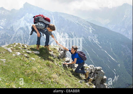 Teenage boys helping friend climbing in mountains - Stock Photo