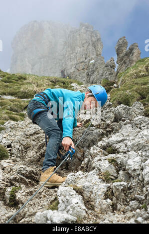 Young teenage boy climbing in mountains - Stock Photo