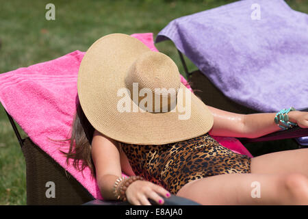 Young woman hiding under sunhat sunbathing on lounger in garden - Stock Photo