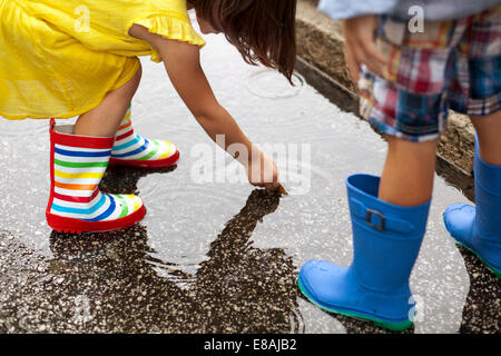 Boy and sister wearing rubber boots looking down at in rain puddle - Stock Photo