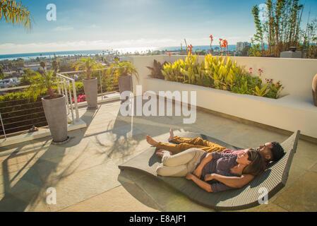 Couple lying on sun lounger in penthouse rooftop garden, La Jolla, California, USA - Stock Photo