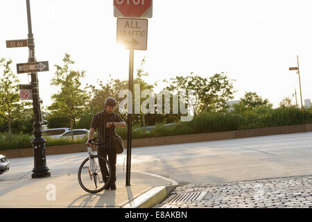 Male cycle messenger checking time on roadside - Stock Photo