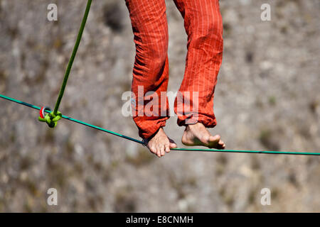 Slacklining is a practice in balance that typically uses nylon or polyester webbing tension between two anchor points. - Stock Photo