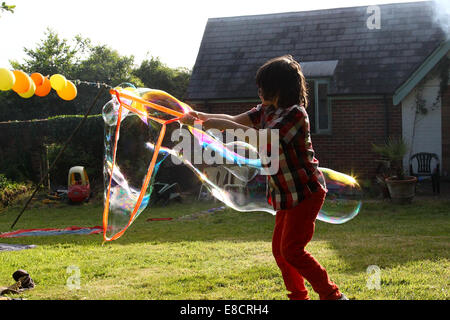 A young child making bubbles in a garden on a summers day During a garden party. - Stock Photo