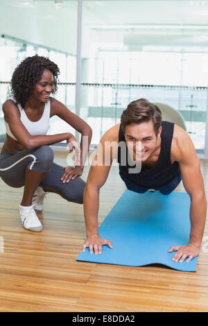 Personal trainer working with client on exercise mat - Stock Photo